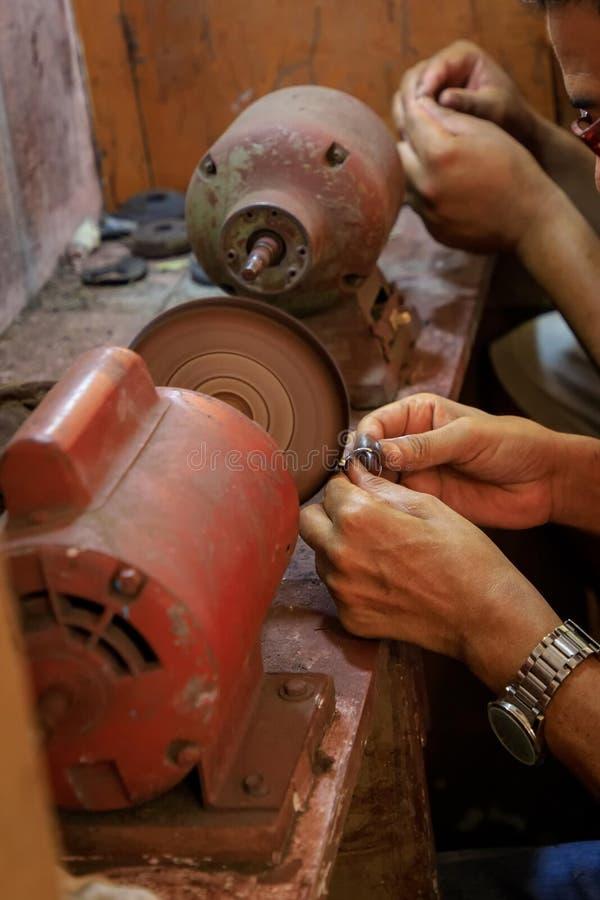 首饰匠擦亮在一擦亮的machin的一个天青石圆环 免版税库存图片