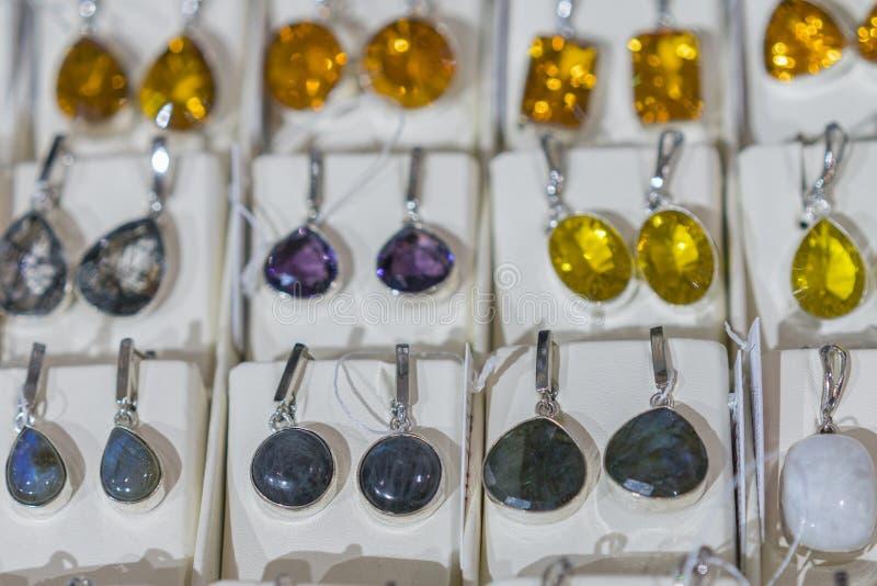 首饰套有石头的耳环用不同的颜色 有石头的集合耳环在商店 库存照片