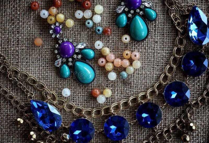 首饰小珠,在棕色大袋背景的耳环链子 设计 免版税图库摄影