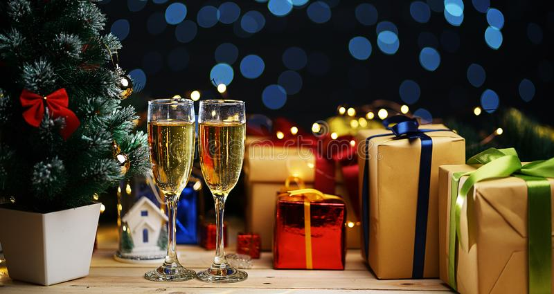 香宾两块玻璃在圣诞树和圣诞节Prese旁边的 免版税图库摄影