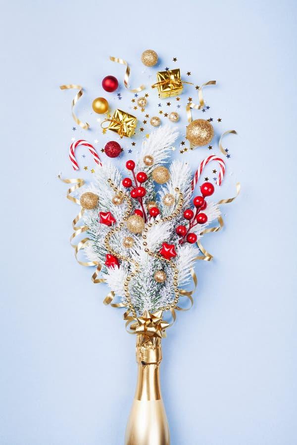 香宾有五彩纸屑、礼物和圣诞装饰的瓶烟花在淡色蓝色背景 平的位置 免版税库存照片