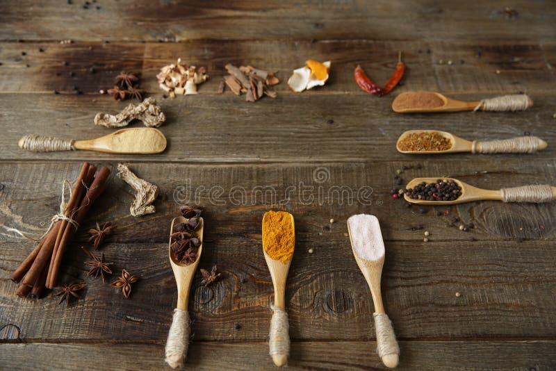 香料分类:姜黄,姜,桂香,肉豆蔻,胡椒,桃红色盐,在木匙子的八角在木背景 免版税库存照片