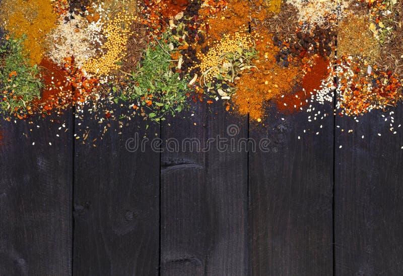 香料和草本在黑暗的木背景 文本的空间 食物框架 与拷贝空间的顶视图 免版税库存照片