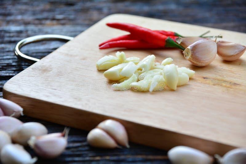 香料辣椒和大蒜在wo上把木切板放 免版税库存照片