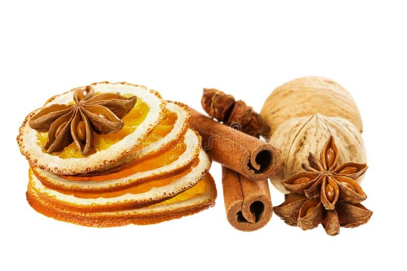 茴香星、在白色背景和干桔子隔绝的肉桂条、核桃 免版税库存照片