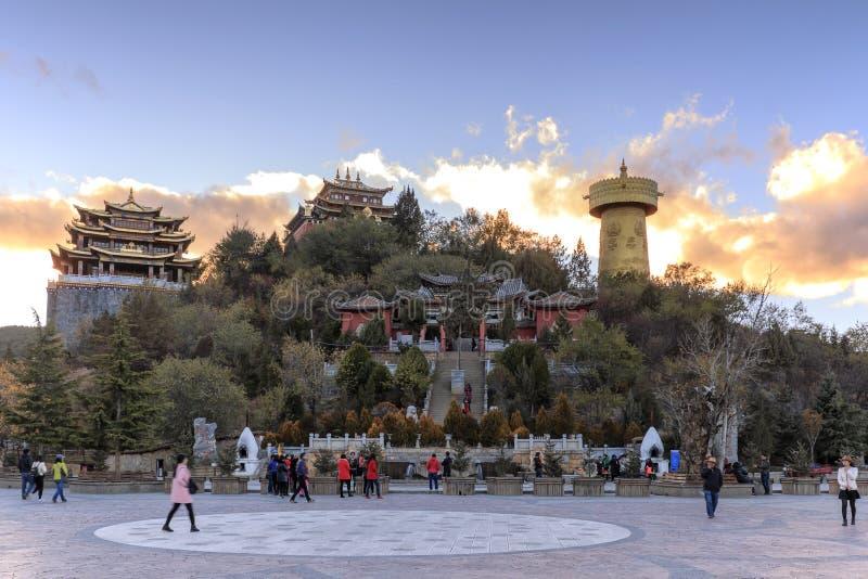 香格里拉金黄寺庙全景在日落的与走有些的游人  图库摄影