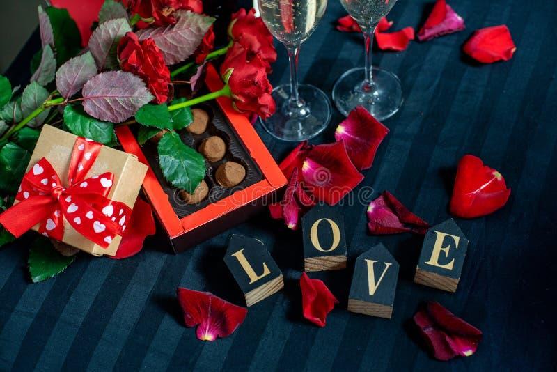 香槟、英国兰开斯特家族族徽、瓣、礼物盒有红色丝带的,巧克力和木爱词两块玻璃在黑背景 库存图片