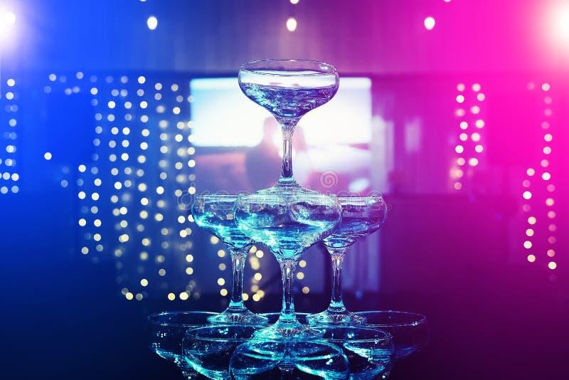 香槟塔顶面排在一个放映机屏幕的theblurred背景的在婚礼宴会大厅里 Beautifull套小轿车gla 免版税库存照片