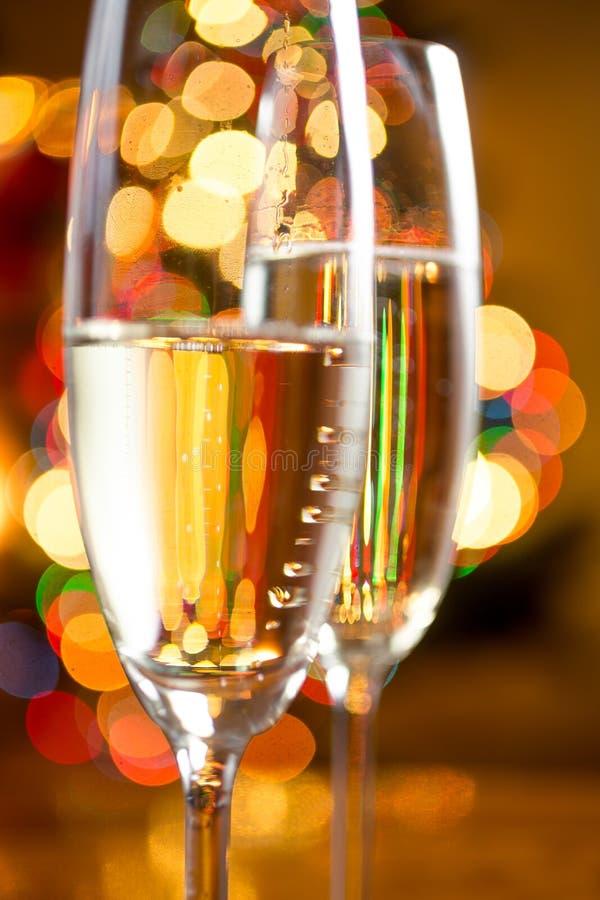 香槟抽象照片在玻璃的反对五颜六色的光 库存照片