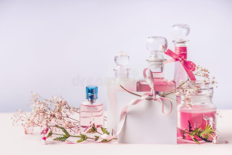 香水和化妆用品暂短气味 瓶和与丝带,正面图的空白的贺卡的构成有花的 免版税库存照片