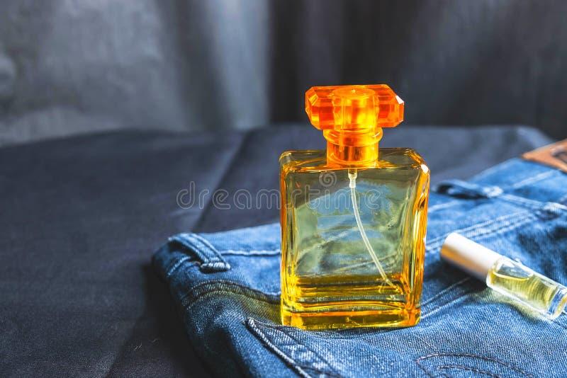 香水瓶和芬芳在牛仔裤袋子 免版税库存照片
