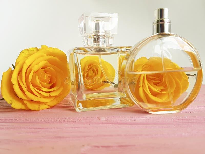 香水瓶在木装饰的黄色玫瑰 图库摄影
