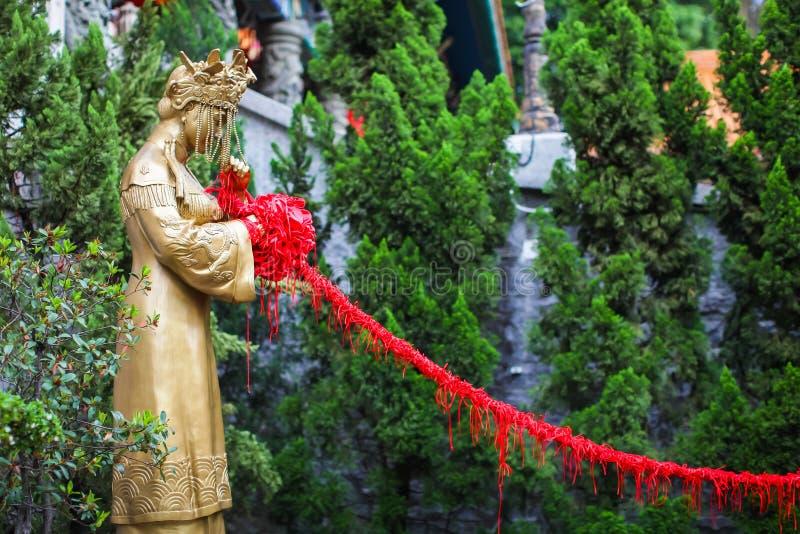 香港,中国- 2018年4月:为与红色丝绸绳索的好爱祈祷在黄大仙祠在香港 新娘雕象  图库摄影