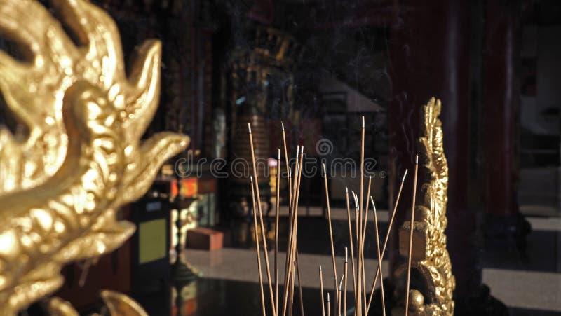 香火棍子特写镜头有烟的在中国寺庙里面 前景有与自然温暖的阳光的中国艺术雕塑 免版税库存照片