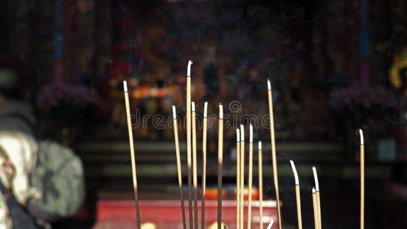 香火棍子特写镜头有烟的在中国寺庙里面 发光通过寺庙内部的自然温暖的阳光 r 免版税库存图片