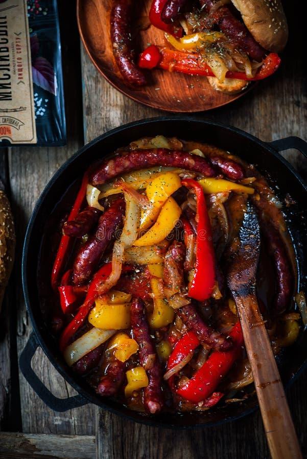 香肠、胡椒和葱在铁平底锅 免版税库存照片