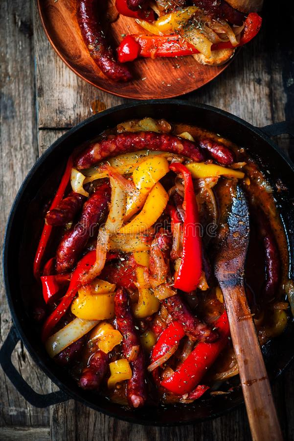 香肠、胡椒和葱在铁平底锅 库存照片