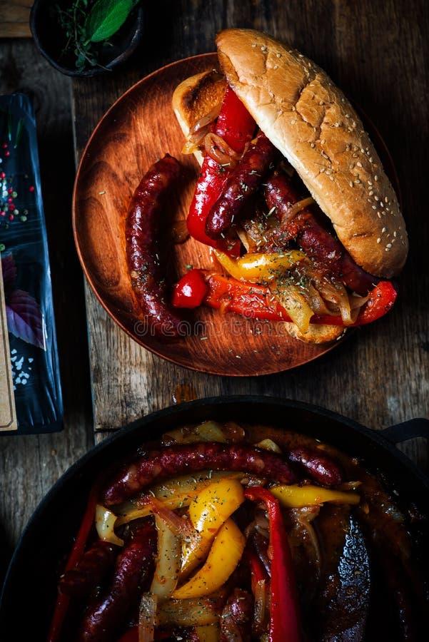 香肠、胡椒和葱在铁平底锅 图库摄影