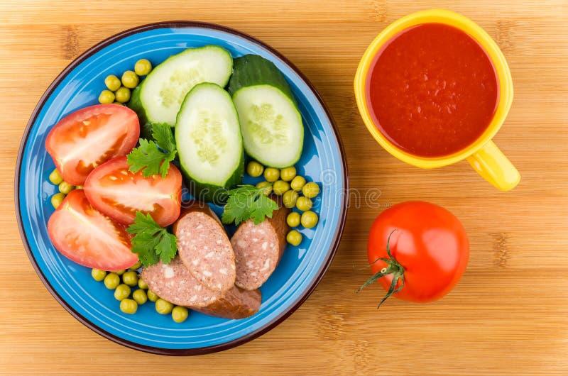 香肠和菜在蓝色板材,西红柿汁在杯子 免版税库存照片