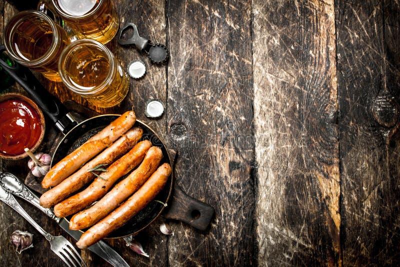 香肠用冰镇啤酒和调味汁 免版税库存图片