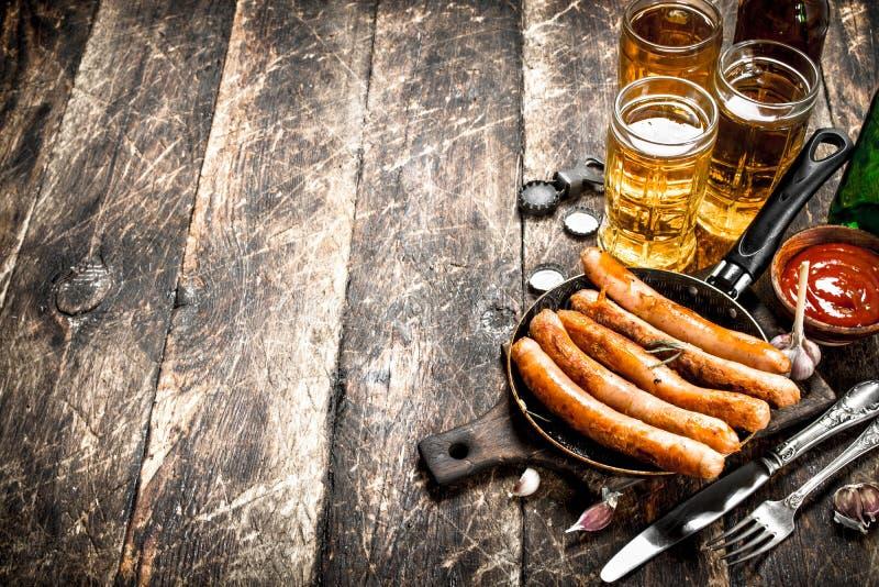香肠用冰镇啤酒和调味汁 库存图片
