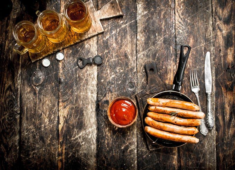 香肠用冰镇啤酒和调味汁 免版税库存照片