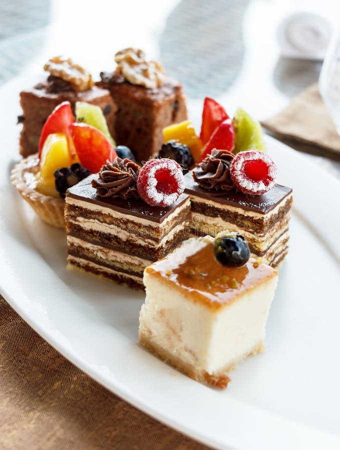 香草乳酪蛋糕用蓝莓 套在分类的微型蛋糕在白色板材 婚姻正餐肉卷熏制的蕃茄 与raspberrie的巧克力蛋糕 库存图片
