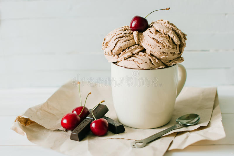 香草圣代冰淇淋冰淇凌用甜樱桃和巧克力在杯子 免版税库存图片