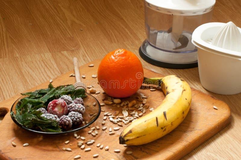 香蕉、桔子、结冰的草莓黑莓和种子生动的圆滑的人成份和搅拌器,榨汁器,在背景的郁金香 库存图片
