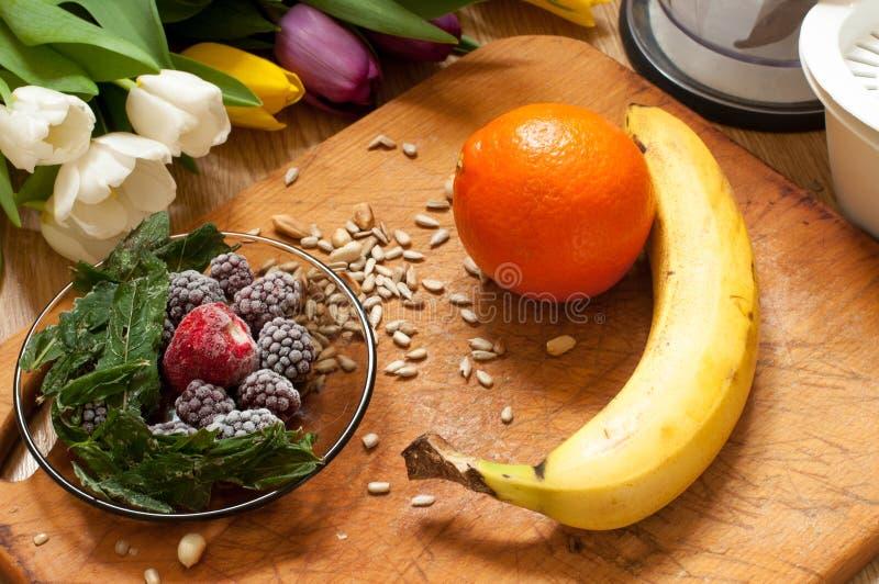 香蕉、桔子、结冰的草莓黑莓和种子生动的圆滑的人成份和搅拌器,榨汁器,在背景的郁金香 免版税库存图片
