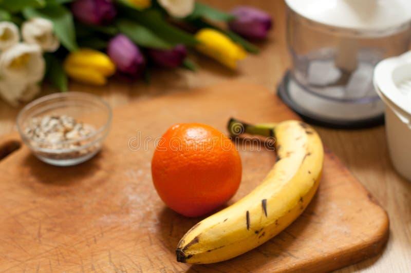 香蕉、桔子和种子生动的圆滑的人成份和搅拌器,榨汁器,在背景的郁金香 库存照片