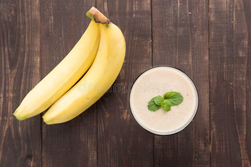 香蕉圆滑的人和新鲜的香蕉在木桌上 图库摄影
