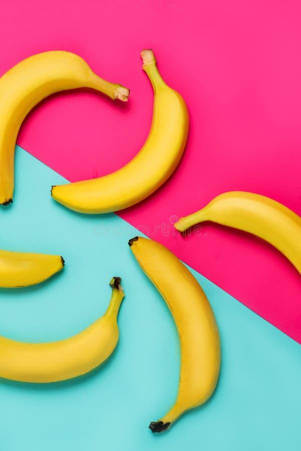 香蕉平的位置在蓝色和桃红色背景的 免版税库存图片
