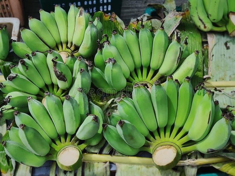 香蕉成堆的绿色香蕉在市场展销 免版税库存照片