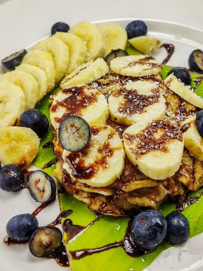 香蕉薄煎饼用巧克力糖浆和蓝莓 免版税库存图片