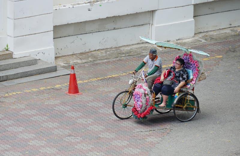 马六甲,马来西亚--2018年2月:一个人踩的踏板与一位女性乘客的一花装饰的trishaw在荷兰正方形在Melaka, 库存图片