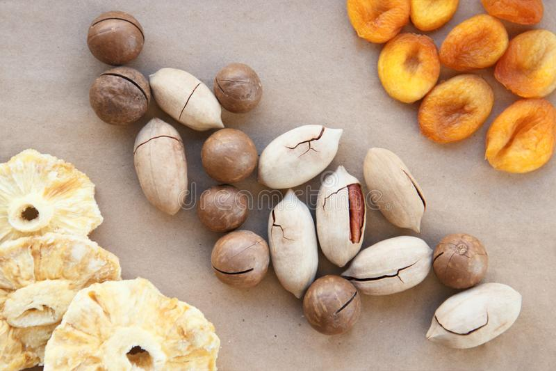 马卡达姆坚果,巴西坚果,贝陀立体,胡桃烘干了菠萝和杏子在棕色包装纸 烤和刻凹痕 免版税图库摄影