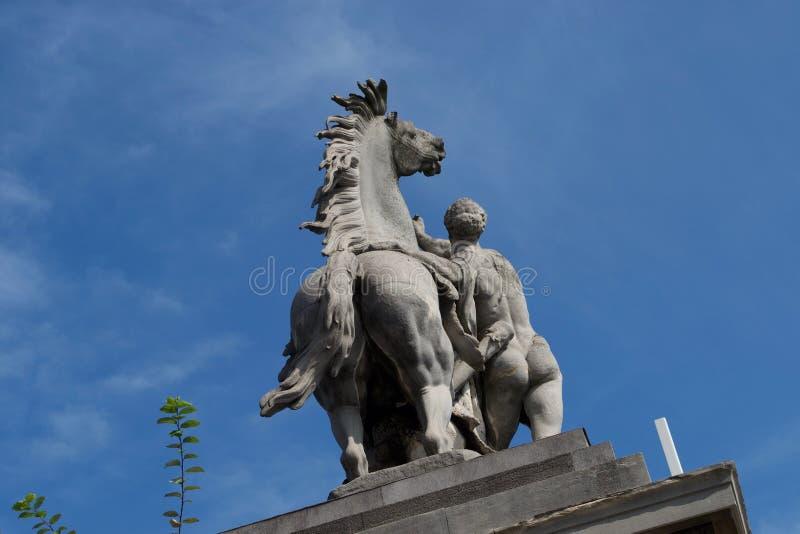 马和人雕象背面图-赤裸反对天空蔚蓝 库存照片