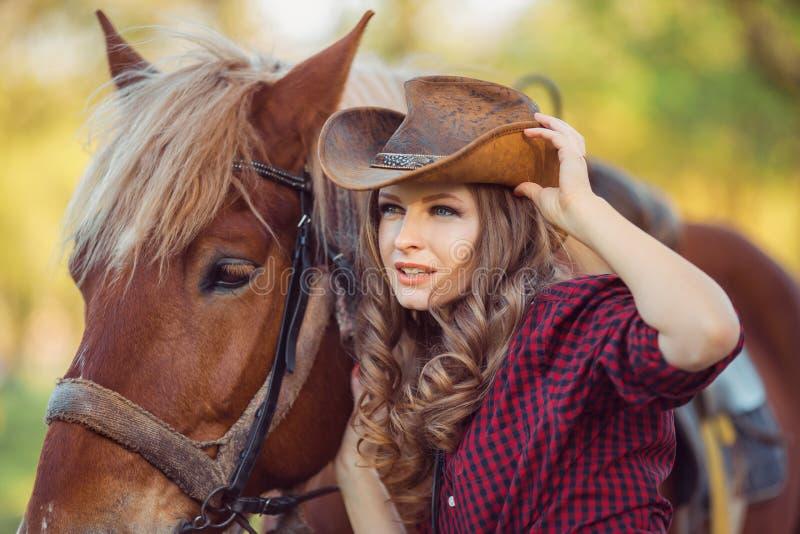马和时装模特儿与牛仔帽 免版税库存图片