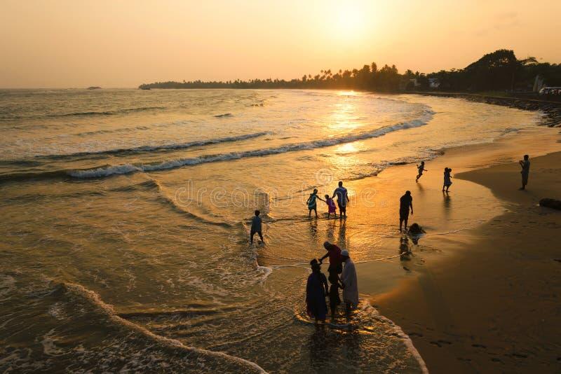 马塔勒,斯里兰卡, 04-15-2017 :金黄日落在海洋的热带 走沿海滩和水的人剪影  库存图片