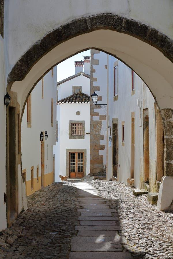 马尔旺,葡萄牙:典型的狭窄修补了有被粉刷的房子和拱廊的街道 库存图片
