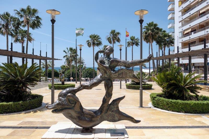 马尔韦利亚, ANDALUCIA/SPAIN - 5月23日:在海豚雕象上的人 图库摄影