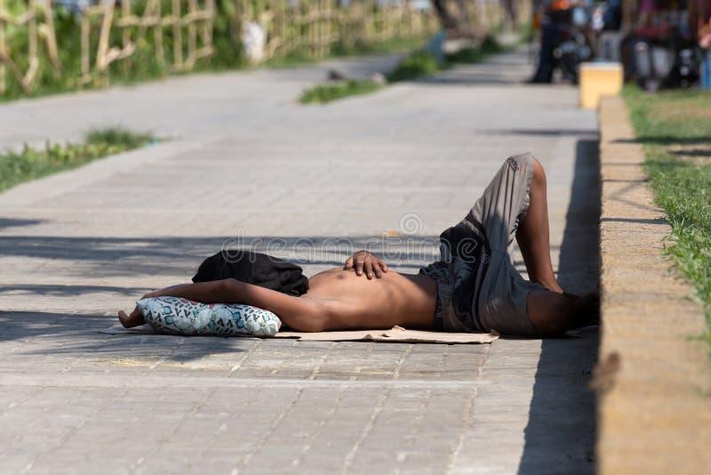 马尼拉,菲律宾- 2019年5月,18日:说谎在马尼拉街道上的一个贫困者,睡觉 免版税库存照片