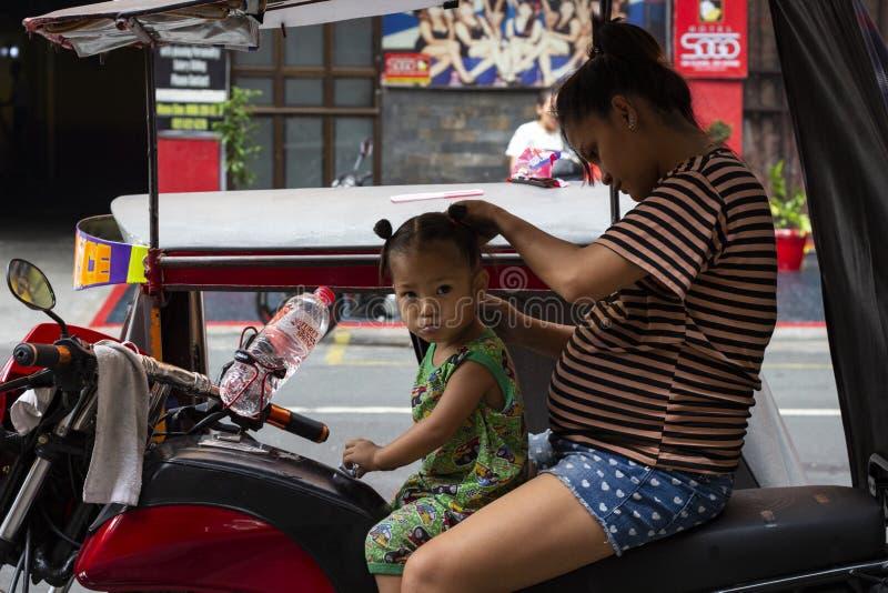 马尼拉,菲律宾- 2018年4月14日:照顾做头发给小女儿在三轮车 可怜的filippino家庭 免版税库存图片