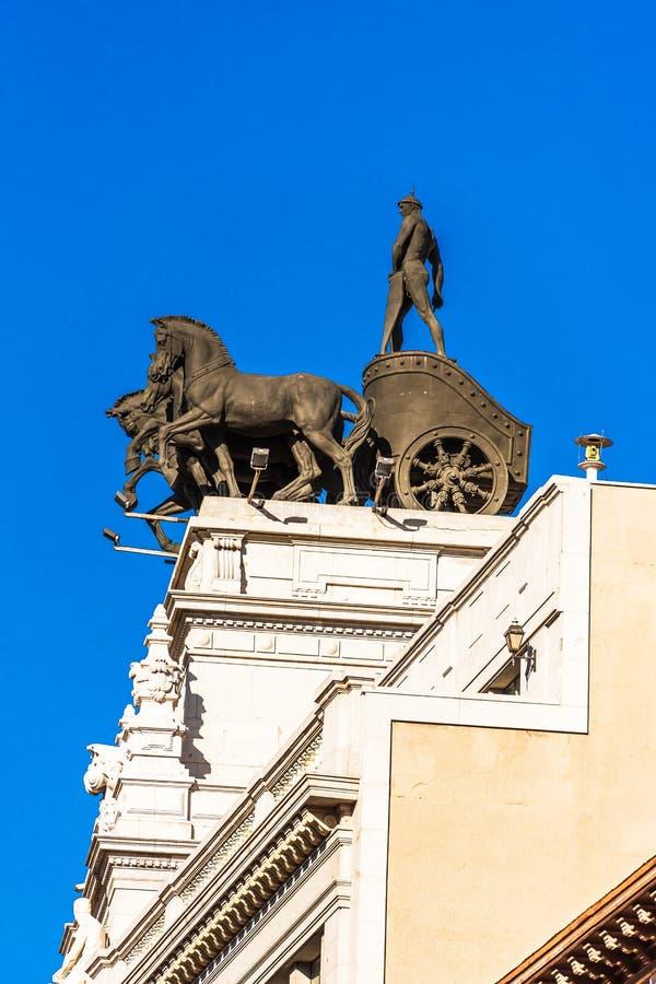 马德里,西班牙- 2017年9月26日:一辆运输车的雕塑,在街道Alcala上的一栋银行大楼 复制文本的空间 Vertic 免版税库存图片