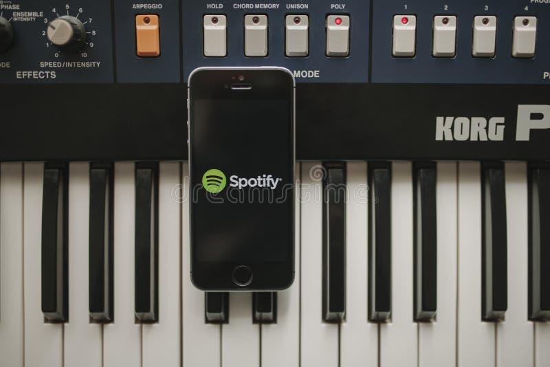 马拉加,西班牙- 2018年4月12日, :放出在iPhone屏幕的Spotify音乐app,安置在葡萄酒音乐会键盘 免版税库存图片