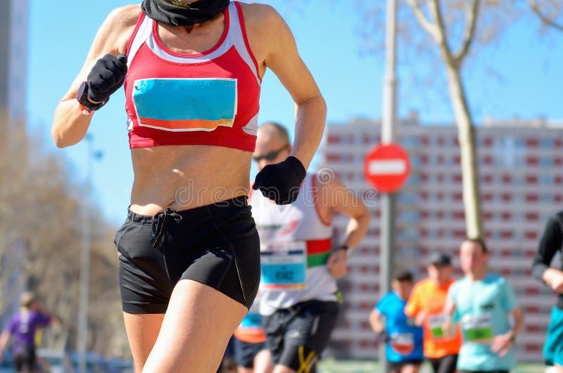 马拉松连续种族,路的妇女赛跑者 免版税库存照片