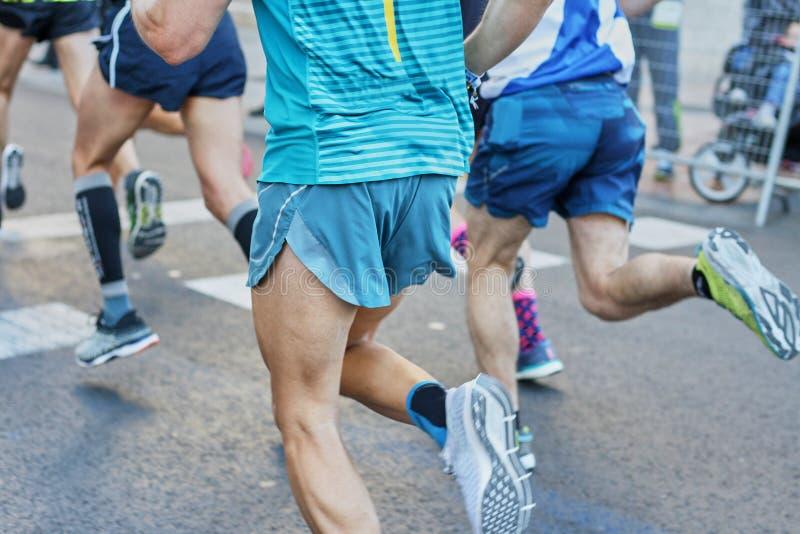 马拉松长跑,跑在城市道路的人的脚 库存照片
