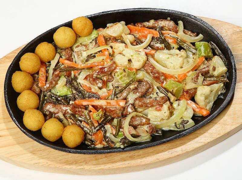 马来西亚式炖牛肉油炸了与蕨、烟肉、硬花甘蓝、花椰菜、葱和红萝卜的牛里脊肉在服务的奶油  库存图片