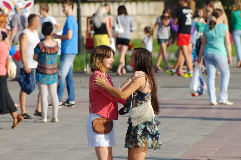 马格尼托哥尔斯克,俄罗斯,- 2014年8月,22日 在走在镇中心的人中的两个女孩跳舞 免版税库存照片